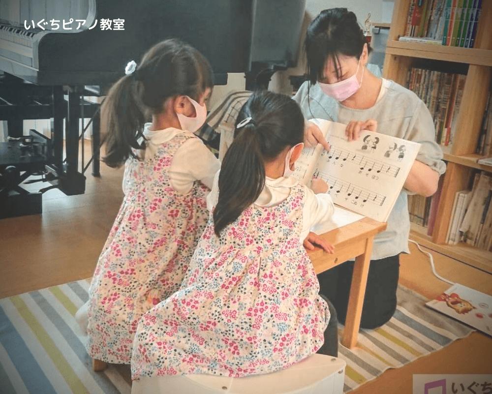 幼児の生徒さんに楽譜を見せながら話をしている画像